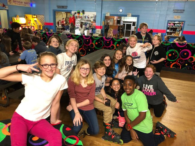 Group of young teens at a roller skating group event.
